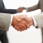 Closeup of business people shaking hands at the workplace